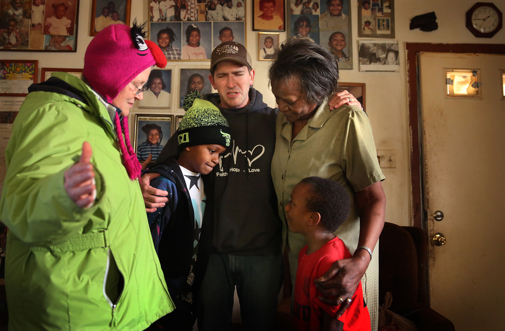 "Levi Vincent, affiliated with the IWorshipCenter as staff Evangelist and missionary to the city of Springfield, conducts a family prayer at center after being invited into the home of Springfield resident Marie Williams at right on Friday, Nov. 20, 2015. The prayer was conducted as part of Vincent's neighborhood outreach ""Bread from Heaven"" ministry, in which he hands out free bread courtesy of Panera Bread. Joining Vincent are fellow iWorship evangelist Mary Taylor at left along with Williams' great grandson Tremell Brooks at center and family friend Jonathan Preister at right. David Spencer/The State Journal-Register"