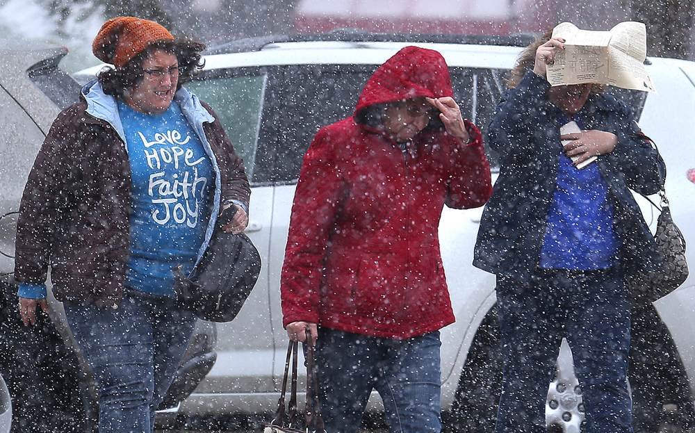 On the Mount Pulaski square on Saturday morning, Nov. 21, 2015, driving snow made for tough going for Helen Roberts at left, Paulette Harper at center and Tracy Bauer at right, who tried using a map featuring vendors for the Christmas on 