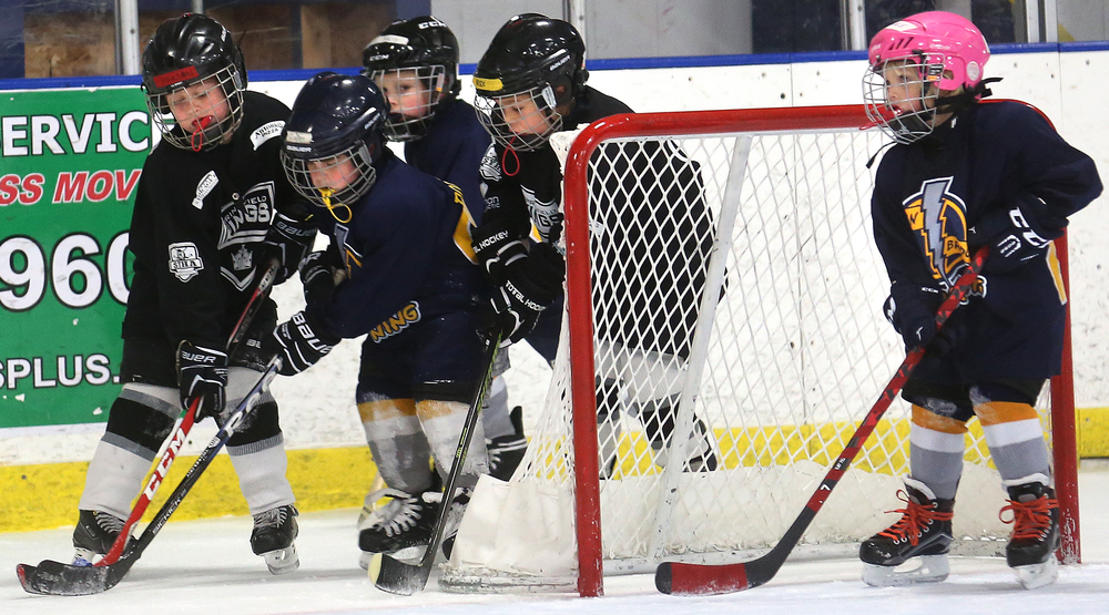 Young hockey players on the Springfield Kings Mini-Mite team compete for control of the puck against the Twin Bridges Lighting based in Granite City, Ill. The games in the Mini-Mite division last 18 minutes and typically feature three or four players facing off against an equal number from an opposing team. The sides switch off every 90 seconds. David Spencer/The State Journal-Register