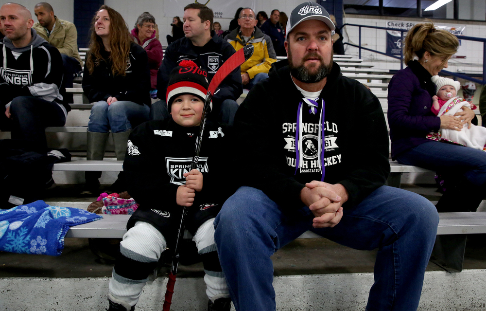 Hockey player Kane Baskett, 5, of Springfield, a member of the Springfield Kings Mini-Mite division team, waits in the bleachers with his dad Brian Baskett before taking the ice. Baskett has played hockey since he was three years old said his dad.  David Spencer/The State Journal-Register