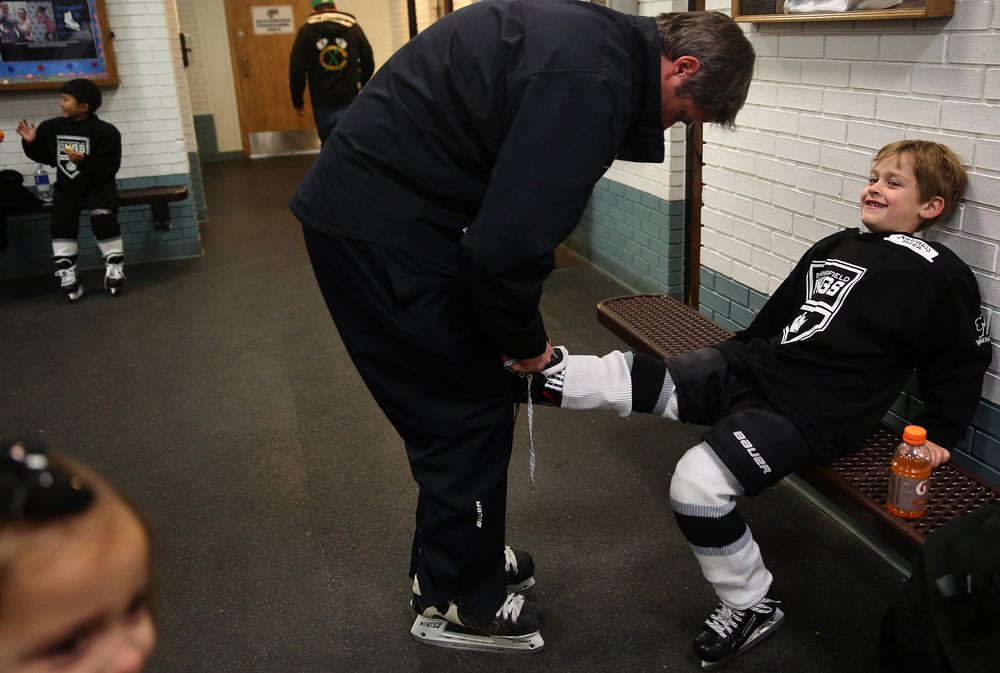 Springfield Kings Mini-Mite team hockey player Kaesen Graff, 6, of Springfield, gets his skates laced up by his father Travis Graff before the start of a game Saturday during the Jamboree. Travis Graff is the head coach of the Springfield Kings Mini-Mite team. David Spencer/The State Journal-Register