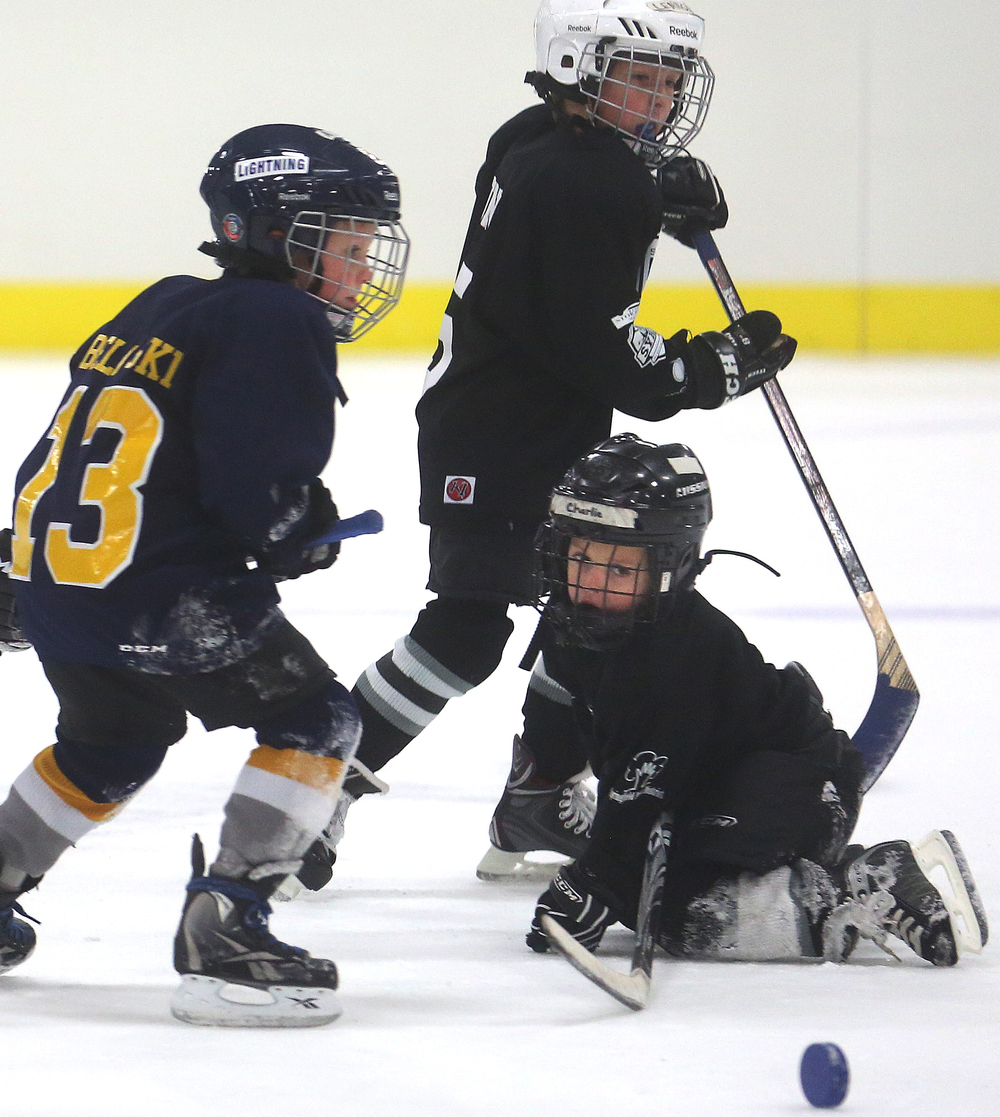 A loose puck gets the attention of a Springfield Kings Mini-Mite hockey player during game action against theTwin Bridges Lightning on Saturday during the Jamboree. David Spencer/The State Journal-Register