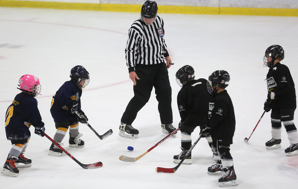 Just like in the big boys games, a sanctioned referee slaps down the puck during a face-off between a Mini-Mite game between the Springfield Kings and Twin Bridges Lightning on Saturday during the Jamboree. David Spencer/The State Journal-Register