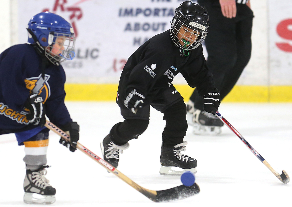A Twin Bridges Lightning Mini-Mite hockey team player tries to keep control of the puck while being pursued at right by a member of the Springfield Kings on Saturday during the Jamboree. David Spencer/The State Journal-Register