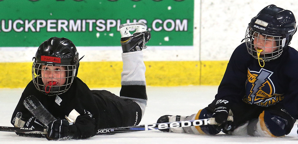 Inevitably, falling down is just part of the job description for hockey players, with young players being no exception. Springfield Kings Mini-Mite player Kaesen Graff, 6 at left, waits a moment along with a player from the Twin Bridges Lightning after both went after the puck at the same time during a game on Saturday. David Spencer/The State Journal-Register