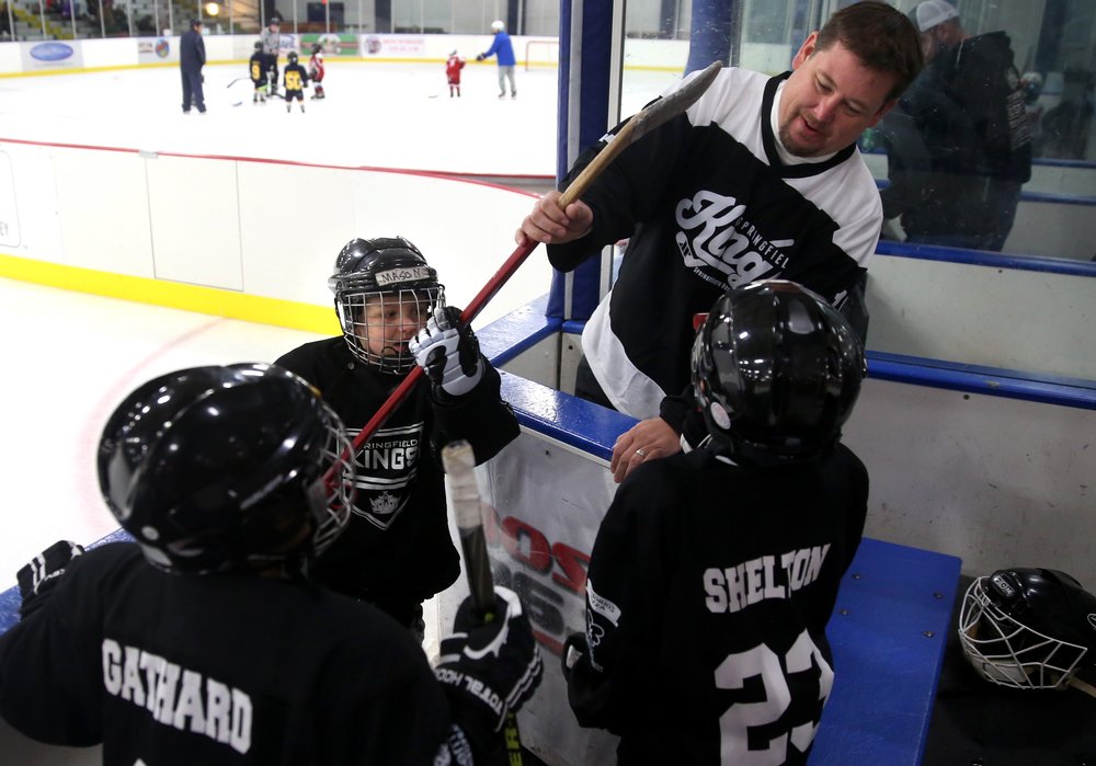 Assistant Springfield Kings hockey coach Brad Gathard had the job of opening and closing the door to the team bench area every 90 seconds as Mini-Mite team members take a breather during an 18 -minute game at the Jamboree. David Spencer/The State Journal-Register