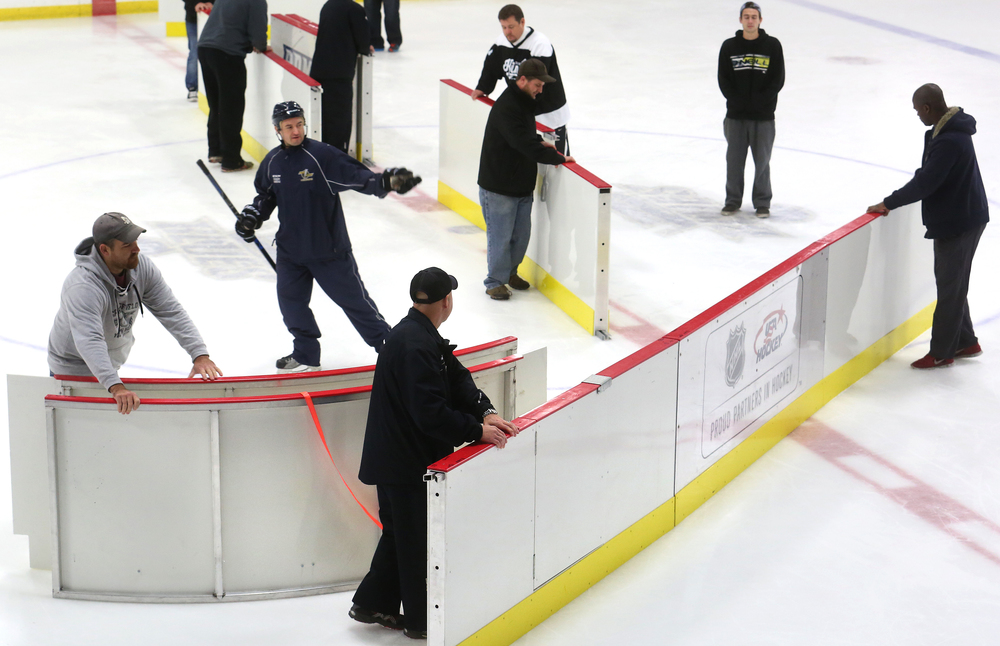 A portable barrier is removed by coaches to make way for the Zamboni. The partition divided the ice rink at the Nelson Center into two playing areas. David Spencer/The State Journal-Register