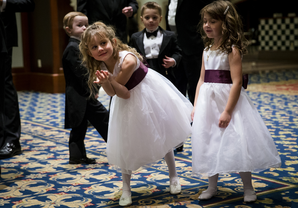 "Rachel Herrin, center, peaks into the ballroom with Alexandra Elliott, right, as they prepare to make their entrance with the Court Children during 84th Beaux Arts Ball, ""The Jewel Ball,"" at the Crowne Plaza Hotel, Saturday, Nov. 28, 2015, in Springfield, Ill. Justin L. Fowler/The State Journal-Register"