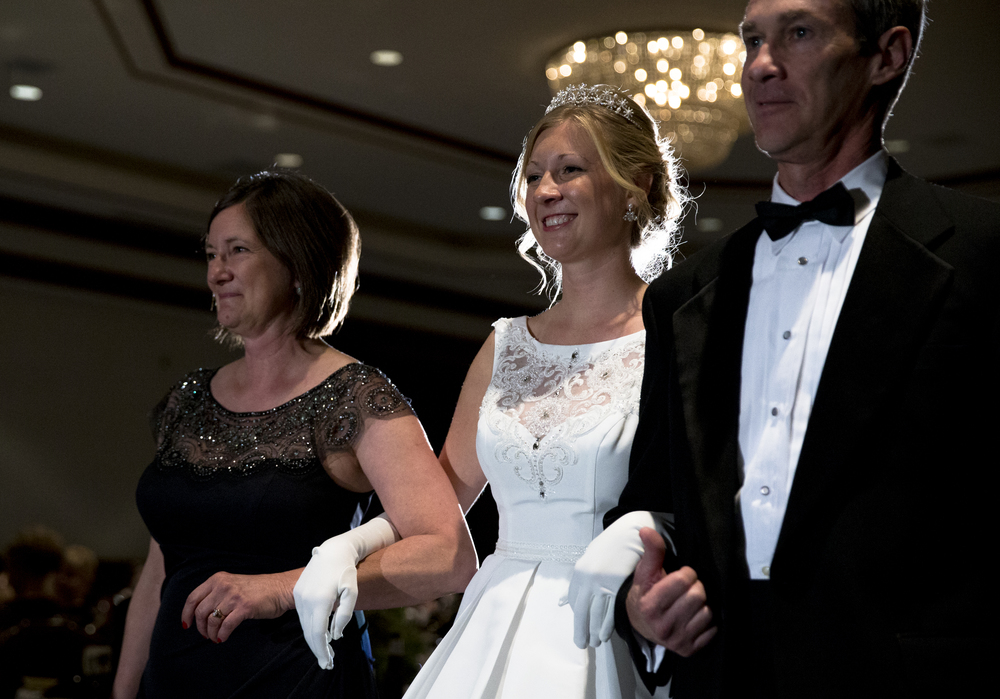 "Queen Christine Rolf, center, is escorted by her parents, David and Alice Rolf, as she makes her opening entrance during the 84th Beaux Arts Ball, ""The Jewel Ball,"" at the Crowne Plaza Hotel, Saturday, Nov. 28, 2015, in Springfield, Ill. Justin L. Fowler/The State Journal-Register"
