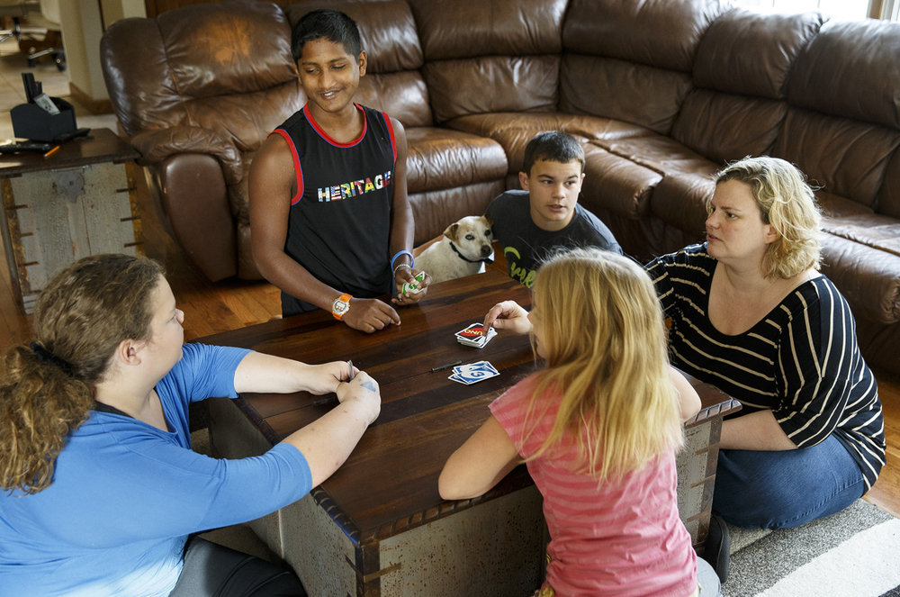 Satchian Basdeo plays cards with the Ferguson family in their Springfield home Tuesday, Nov. 25, 2015. Basdeo, was brought from Guyana to Springfield by Dr. Kristen Ferguson, right, for free cleft palate surgery, is on track to be adopted by the family sometime in 2016.  Ted Schurter/The State Journal-Register
