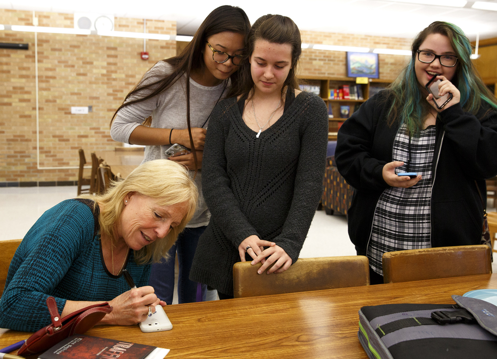 Ellen Hopkins, a bestselling author who writes novels popular with teens and young adults, autographs a cell phone that belongs to Sydney Justus, center, Tuesday, Nov. 17, 2015 at Southeast High School. Watching are Lillian Ye, left, and Ericka Creek. Rich Saal/The State Journal-Register