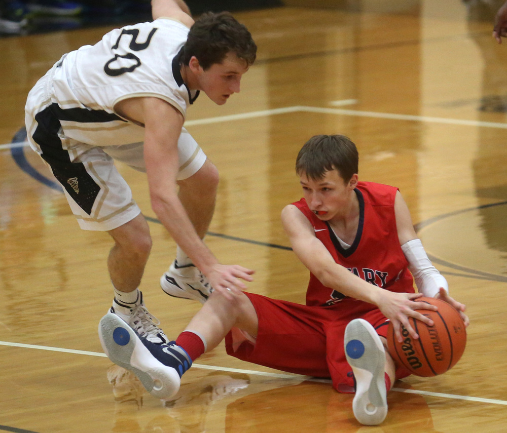 Saints player Colton Larson looks to get rid of the ball from the floor under pressure from Cyclones defender Dustin Moles.David Spencer/The State Journal-Register
