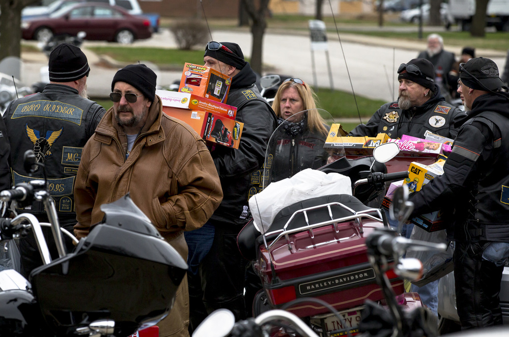 Motorcycle riders from all around central Illinois gather toys from their bikes as they make the delivery to Contact Ministries during the 32nd Sid Wood Memorial Toy Run, Sunday, Nov. 29, 2015, in Springfield, Ill. Justin L. Fowler/The State Journal-Register