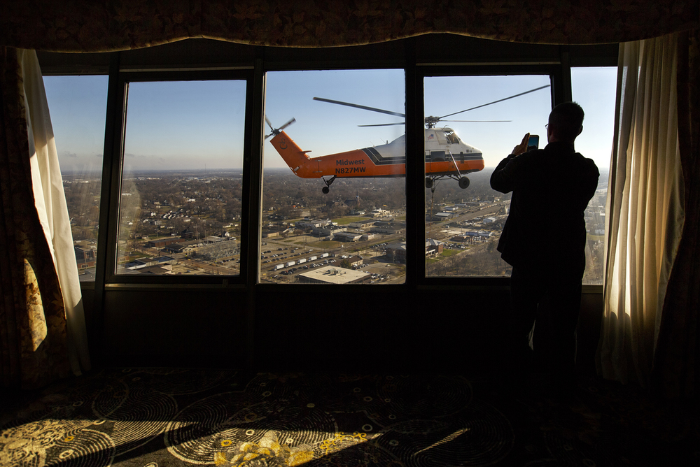 Khris Donaldson watches a Sikorksy S-58T helicopter glide past a window near the top of The Hilton Springfield Friday, Dec. 4, 2015. The Midwest Helicopter Airways helicopter, based out of Willowbrook, Ill. and capable of lifting loads up to 4,500 lbs., was lifting communications equipment to the top of the 30-story hotel. Ted Schurter/The State Journal-Register