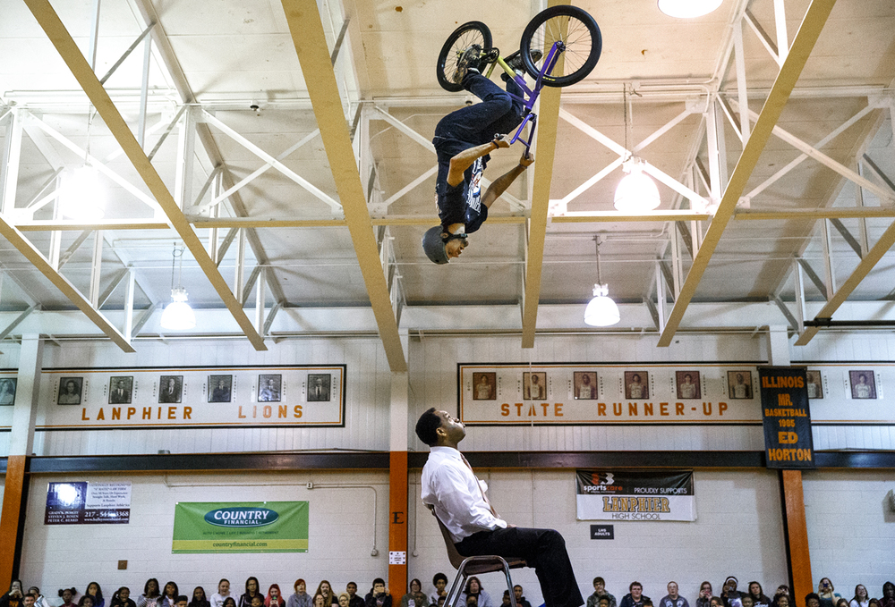 "Lanphier High School principal Artie Doss looks up at BMX stunt rider Allen Adams as he sails upside down over his head during the Army National Guard ""Bring Your 'A Game' to School"" BMX demonstration Monday, Nov. 30, 2015. Adams and two other stunt riders entertained students with high flying acrobatics and BMX stunts. Ted Schurter/The State Journal-Register"
