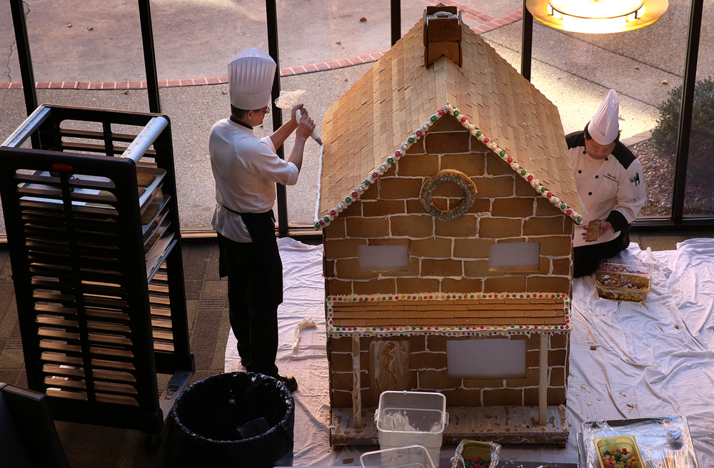 Chef Keith Loukinen uses a pastry bag to apply icing to the roof line of the gingerbreak house at left on Tuesday afternoon while Executive Sous Chef Walter Rivas works at assembling the rear of the house at right. For the second year, downtown Hilton Hotel Executive Chef Keith Loukinen has built a large gingerbread house along with his staff in the Hilton lobby area. On Tuesday, Dec. 1, 2015, the house was assembled where it will be on public display until just before New Year's Eve. Loukinen said hotel pastry chef Katie Banning has been baking gingerbread for the house between other duties for the past several weeks. The eight ft. by eight ft. house will be lighted from the inside and feature a chocolate sleigh on the roof, which is covered with graham crackers, along with decorations featuring candy embedded in white icing along the roof lines and around a front porch.  David Spencer/The State Journal-Register