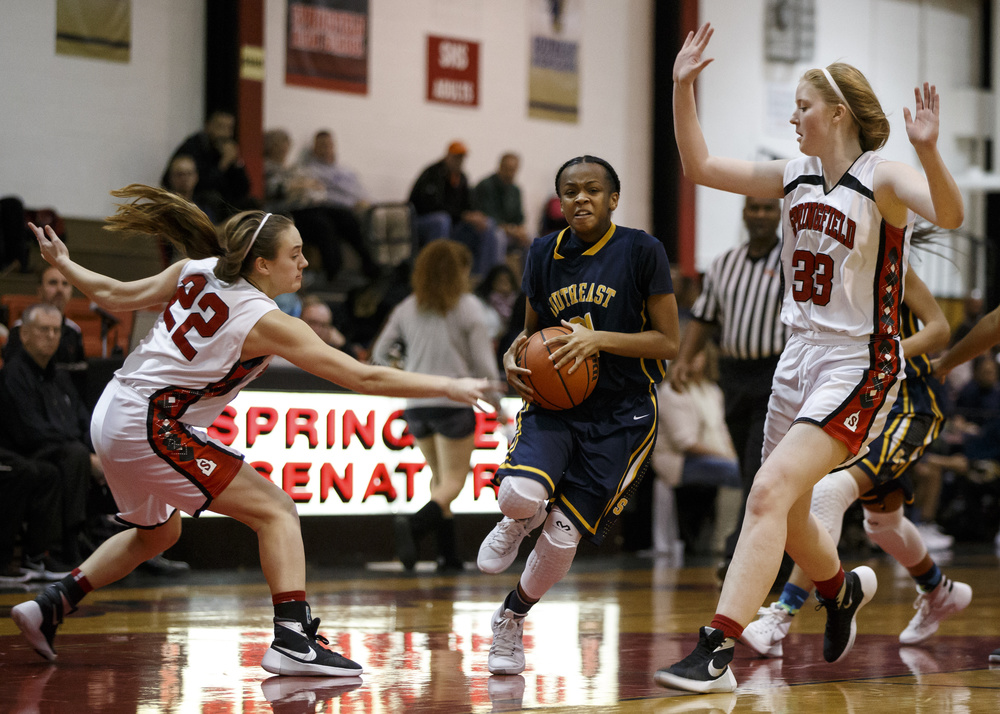 Southeast's Adriana Brown (21) drives towards the basket avoiding the pressure from Springfield's Sarah Cross (22) in the first half at Springfield High School, Thursday, Dec. 10, 2015, in Springfield, Ill. Justin L. Fowler/The State Journal-Register