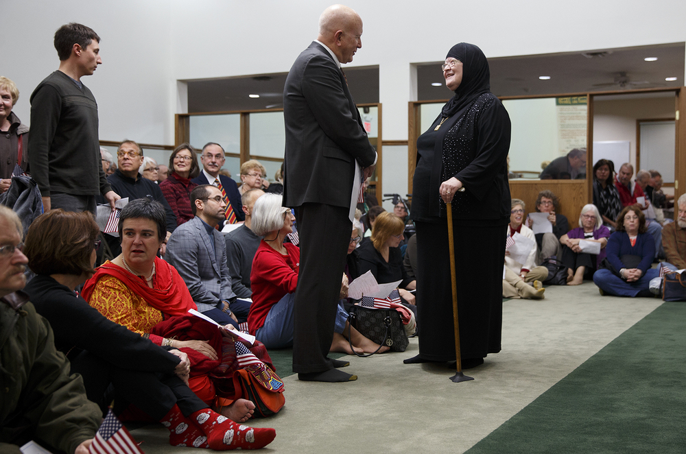 Maryam Mostoufi, Chaplain of the Islamic Society of Greater Springfield, greets Jim Lewis, the U.S. Attorney General for the Central Illinois District at the Interfaith Peace Vigil sponsored by the Islamic Society at their masjid Sunday, Dec. 13, 2015. Ted Schurter/The State Journal-Register