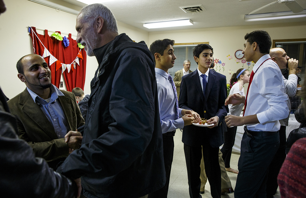 Malik Siddique, center visits with Amr Issa, left, and Faris Shaikh as they enjoy refreshments after the Interfaith Peace Vigil at the Islamic Society of Greater Springfield's masjid Sunday, Dec. 13, 2015. Ted Schurter/The State Journal-Register
