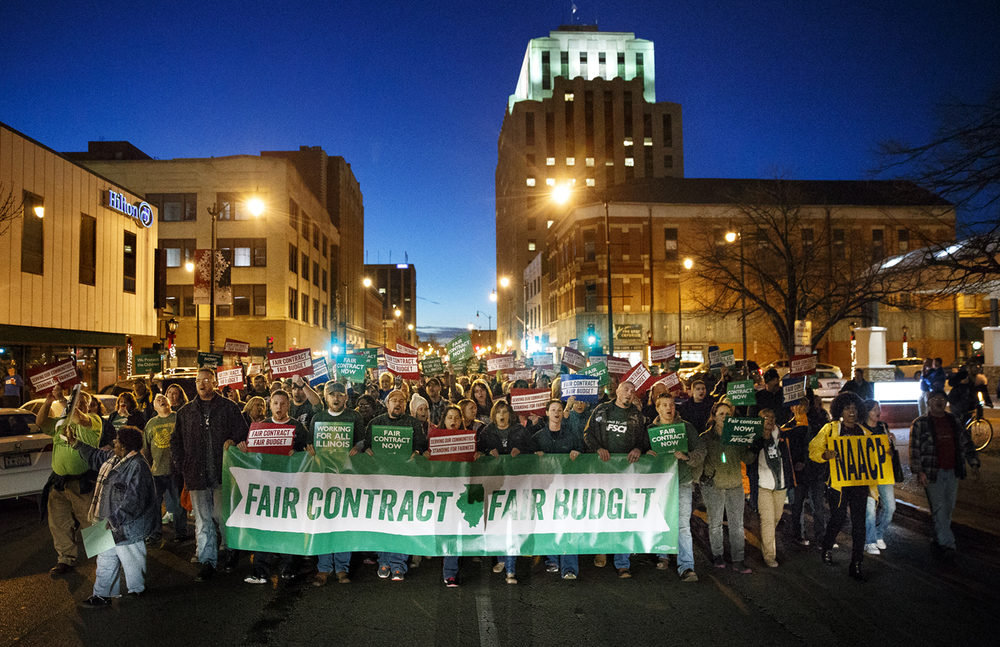 "Demonstrators chant and wave signs as they make their way down Adams Street to the Prairie Capital Convention Center to participate in one of the American Federation of State, County and Municipal Employees' seven statewide ""Rallies for Fairness"" Thursday, Dec. 10, 2015. Ted Schurter/The State Journal-Register"