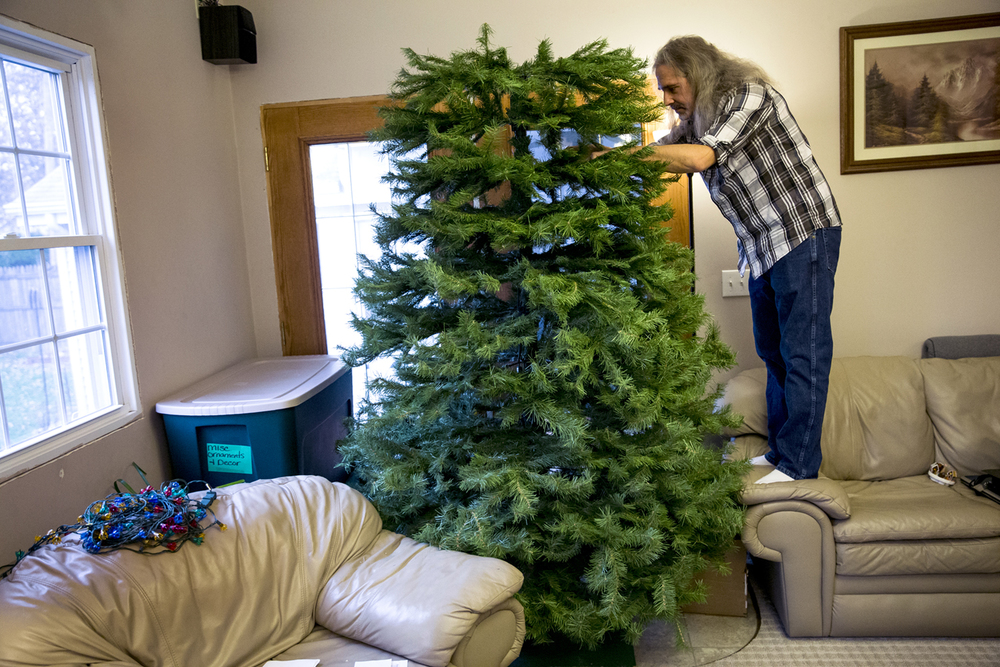 Matt Crocker goes through the branches of a donated 9ft tall artificial Christmas tree to ensure that all the pieces are in place as he and his wife, Kathy, prepare it for a new home through their Trees With Love program at their home, Thursday, Dec. 10, 2015, in Pawnee, Ill. Matt and Kathy Crocker take donated artificial trees and provide the trees along with lights and ornaments to families in need. Justin L. Fowler/The State Journal-Register