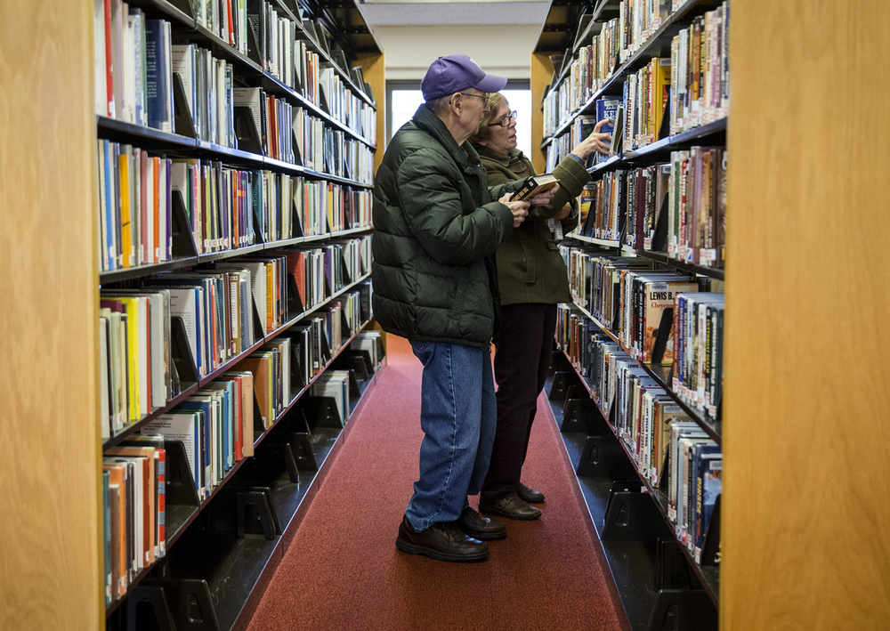 Carol and Wayne Moore look through the shelves in the large print fiction section at the Springfield Public Library, Friday, Dec. 11, 2015, in Springfield, Ill. The couple are avid users of both the Springfield Public Library and Chatham Public Library and enjoy reading a physical book over a digital copy. Justin L. Fowler/The State Journal-Register