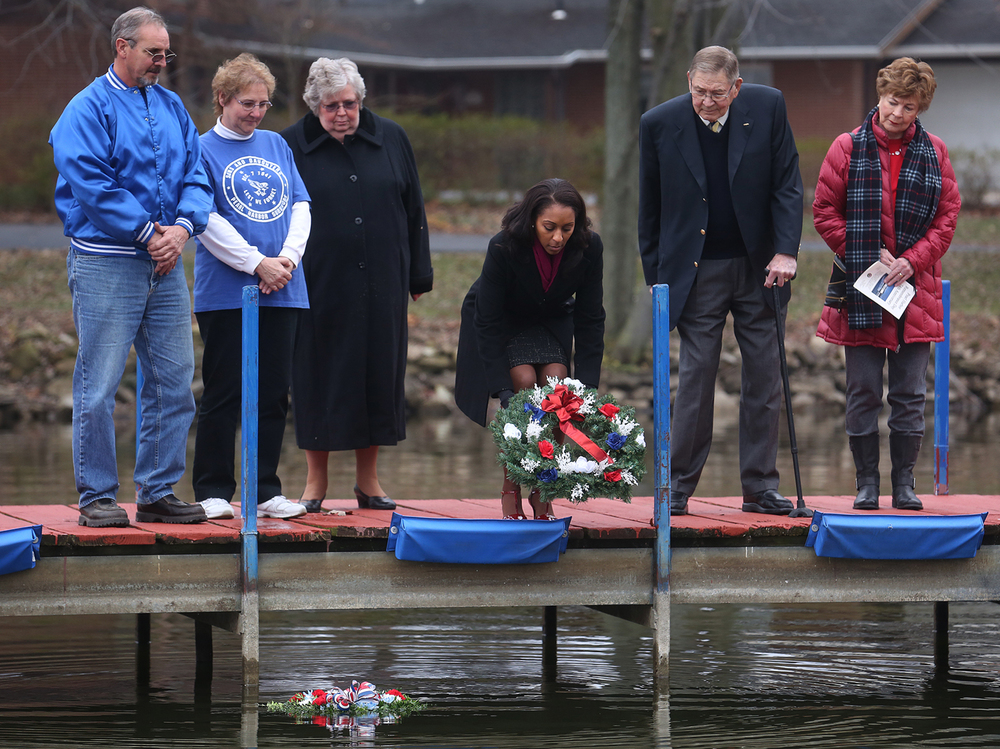 Erica Jeffries, Director of the Illinois Department of Veterans' Affairs, tosses one of the memorial wreaths into Lake Springfield in memory of those killed in the 1941 Pearl Harbor attack. Looking on from left to right are: Sons and Daughters of Pearl Harbor Survivors Illinois president Steve Browning of Mattoon, organization member Charlotta Janes, Gwen Diehl, Illinois Department of Veterans' Affairs Chief of Staff, retired U.S. Navy Vice Admiral Ron Thunman of Springfield and his wife Owsley Thunman. A ceremony marking the 74th anniversary of the attack on American naval forces at Pearl Harbor took place at the Disabled American Veterans Hall at Lake Springfield on Monday, Dec. 7, 2015. Retired U.S. Navy Vice Admiral Ron Thunman of Springfield was the keynote speaker for the event. David Spencer/The State Journal-Register