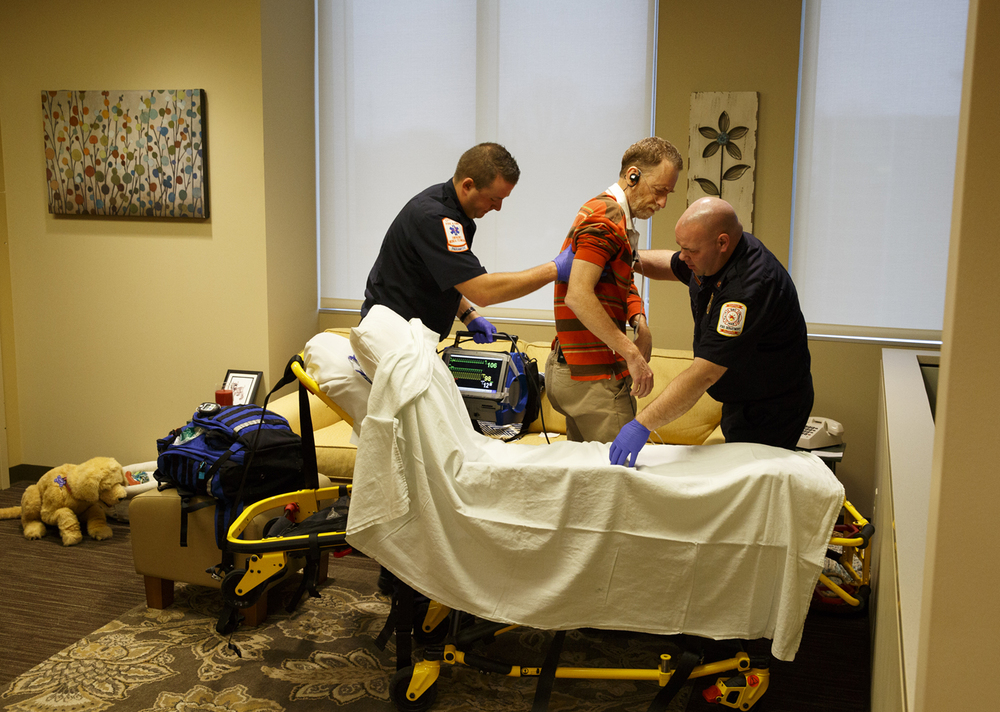 Kyle Enstrom, left, and Jimmy Gerberding, paramedics with the Chatham Fire Department, transfer patient actor John Petter to an ambulance cot after responding to his call for medical help in a training simulation at the Center for Learning and Innovation at Memorial Medical Center Thursday, Dec. 17, 2015. The simulation began with Petter's call and followed it through diagnoses and treatment. Rich Saal/The State Journal-Register