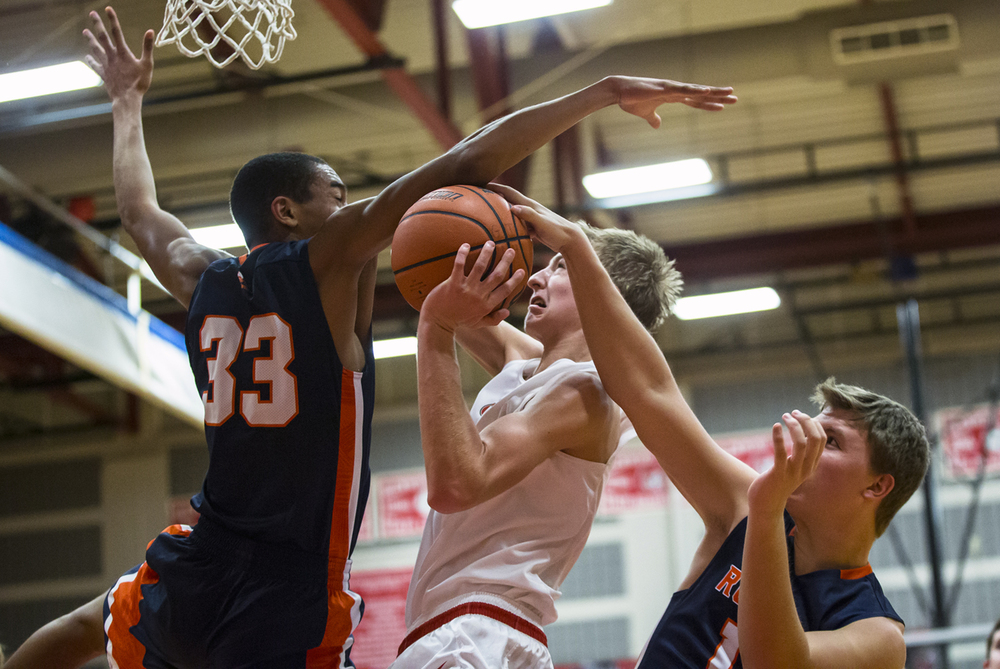 Glenwood's Karson Aherin (12) draws the foul as he goes for a shot against Rochester's Collin Stallworth (33) and Dan Zeigler (12) in the second half at Glenwood High School, Friday, Dec. 18, 2015, in Chatham, Ill. Justin L. Fowler/The State Journal-Register