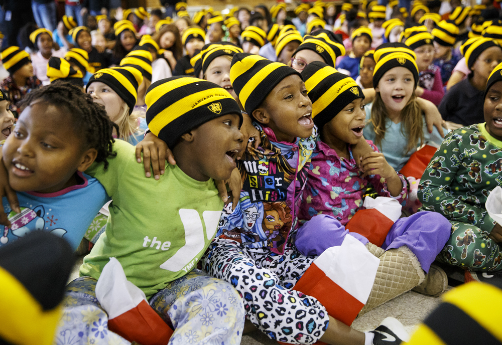 Wearing their brand-new Harvard Park Elementary stocking caps, students, from left, Syrena King, Mar'riyonna Robinson, Na'talyah Green and A'Nijah Wallace link arms as they sing Christmas carols after Santa Claus and more than a dozen Horace Mann volunteers handed out stockings Friday, Dec. 18, 2015. Ted Schurter/The State Journal-Register