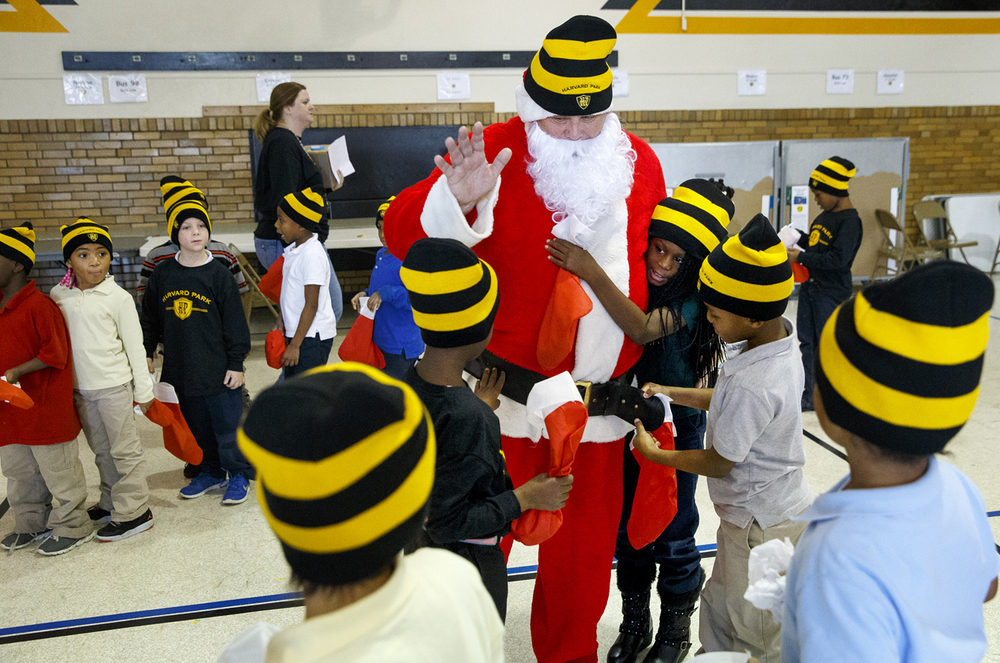 "Harvard Park Elementary School students hug Santa Claus as they prepare to head back to their classrooms after he delivered stockings stuffed with warm Harvard Park stocking caps, some puzzles and a candy cane for each student with the help of more than a dozen Horace Mann volunteers Friday, Dec. 18, 2015. The gifts are the fruit of the companies' annual ""Giving Tree"" campaign. Ted Schurter/The State Journal-Register"