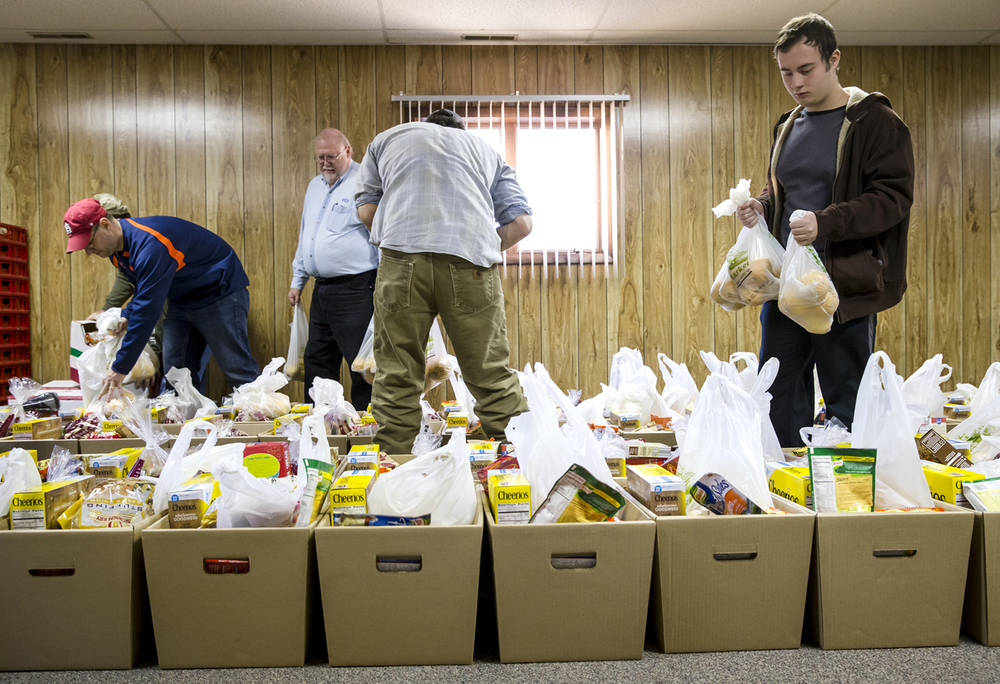 Brandon Maxey, right, packs oranges into food baskets at the Pawnee Township Hall prior to the delivery to those in need by the Pawnee Lions Club for their Christmas food basket project, Saturday, Dec. 19, 2015, in Pawnee, Ill. Justin L. Fowler/The State Journal-Register
