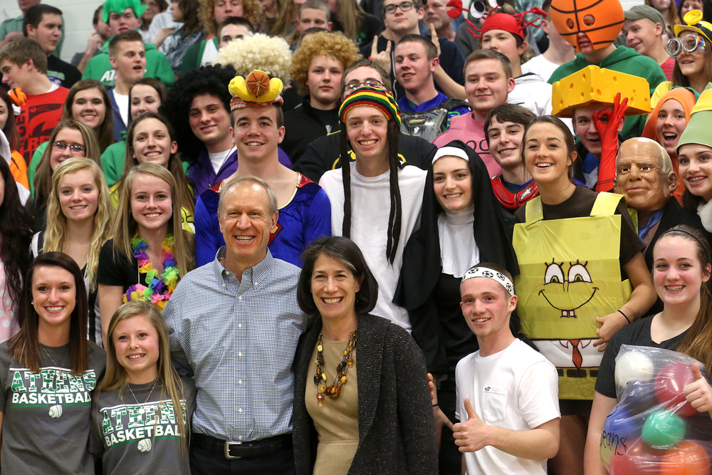 Before the start of the game, Illinois Gov. Bruce Rauner and wife Diana Rauner pose for photos with members of the Athens student cheering section who were dressed up as part of senior night festivities. Petersburg PORTA defeated Athens 64-32 in boys basketball action at Athen's gym in Athens on Tuesday evening, Feb. 3, 2015. David Spencer/The State Journal-Register