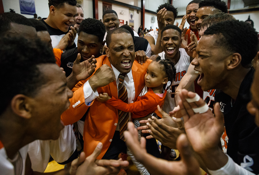 Lanphier head coach Blake Turner, along with his daughter Chelsea, 4, celebrates with the Lions after they defeated Southeast 81-80 to win the Class 3A Springfield Regional title game at the Willard Duey Gymnasium, Friday, March 6, 2015, in Springfield, Ill. Justin L. Fowler/The State Journal-Register
