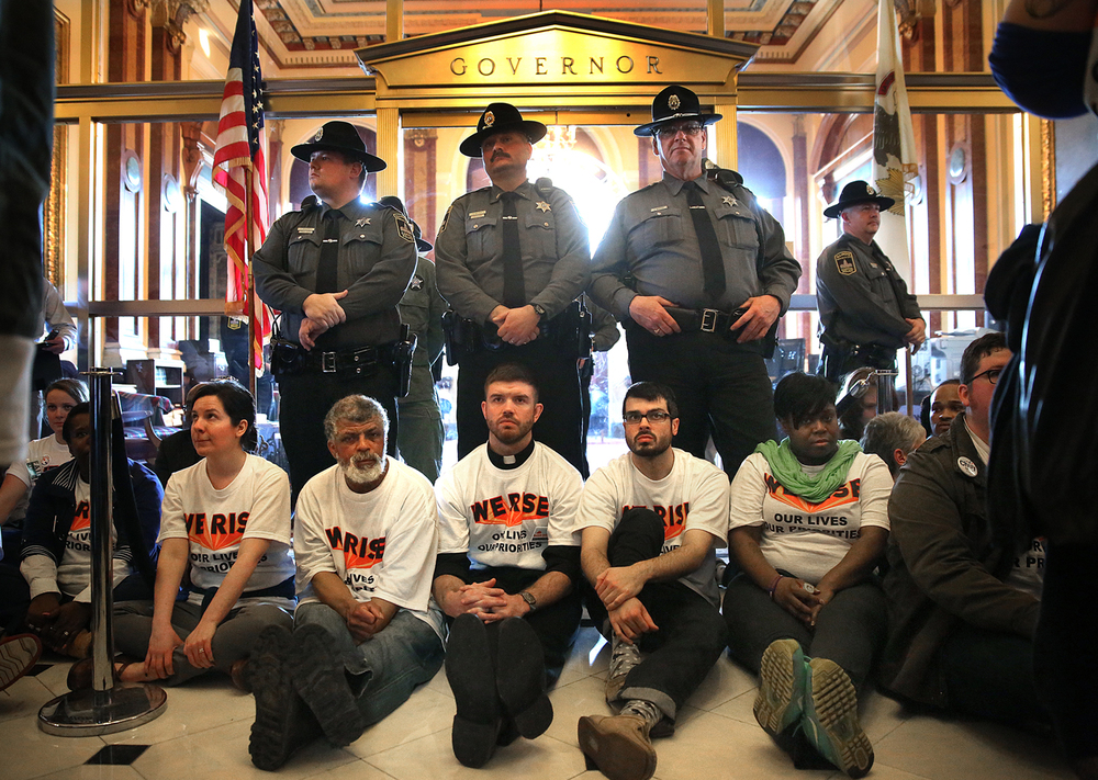 "In an act of civil disobedience, protestors sat together in front of the Governor's office inside the Capitol building while Secretary of State police stand guard behind them on Wed. March 11, 2015. As part of ""We Rise"", a national day of action targeting state budget cuts, several thousand people from faith, community and labor organizations including adults, children and clergy affected by Gov. Bruce Rauner's proposed cuts gathered in Springfield to protest. The event began with a rally inside the Capitol building followed by a march to the governor's mansion where a mock ""funeral"" for the ""99%"" took place. David Spencer/The State Journal-Register"
