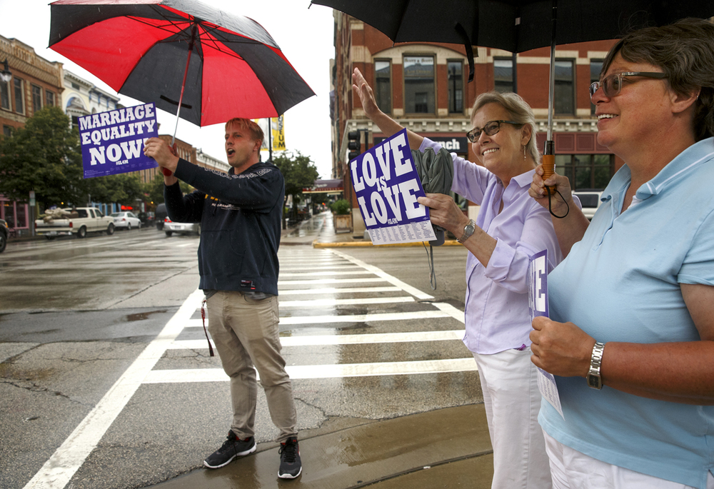 Rhonda Jenkins waves at a honking motorist as she stands with Scott Cross and Ramona Boston at the intersection of Sixth Street and Monroe Street to celebrate the Supreme Court ruling today legalizing same-sex marriage. Ted Schurter/The State Journal-Register
