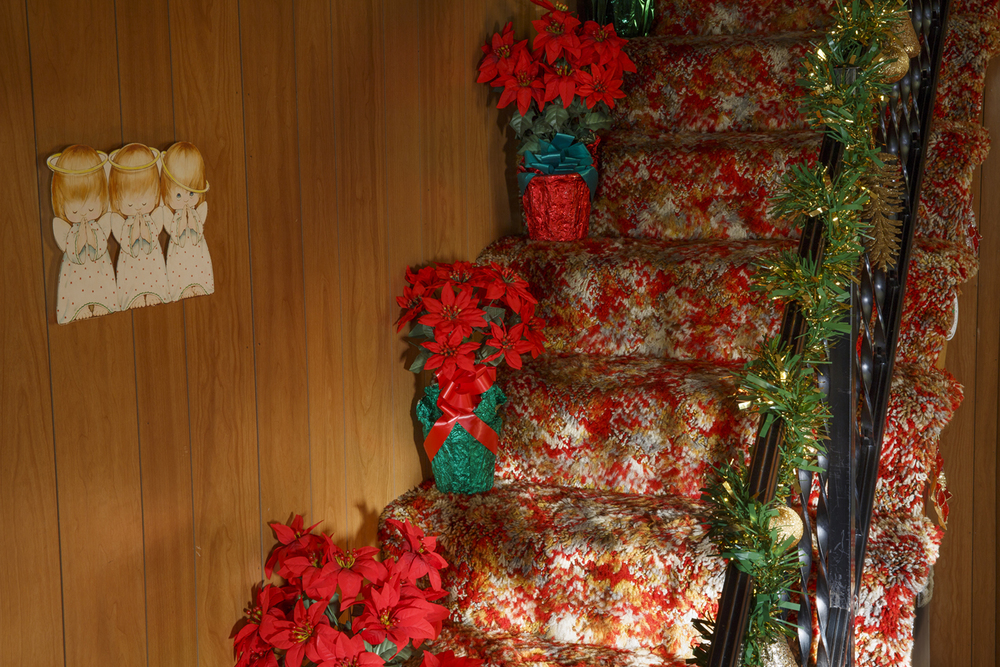 The stairs and railing in Jean Hulbert's home is decorated with poinsettias and artificial evergreen garland. Rich Saal/The State Journal-Register