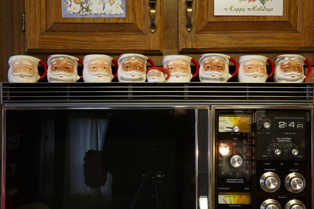Santa mugs line the top of a microwave oven in Jean Hulbert's kitchen.
