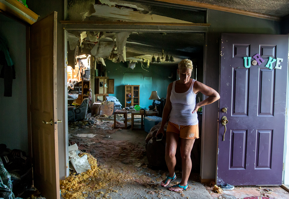 Jessica Burke walks through the water soaked carpet covered in insulation as family and friends help to salvage her possessions, along with those of her husband and three children, the day after a fire destroyed their home, Wednesday, July 29, 2015, in Curran, Ill. Justin L. Fowler/The State Journal-Register