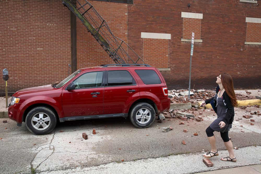 Emily Dorsey warily approaches her Ford Escape before driving it away from the building at 301 E. Monroe Tuesday July 7, 2015. Dorsey's car was damaged when bricks fell from the roof on the building hitting her car. Rich Saal/The State Journal-Register
