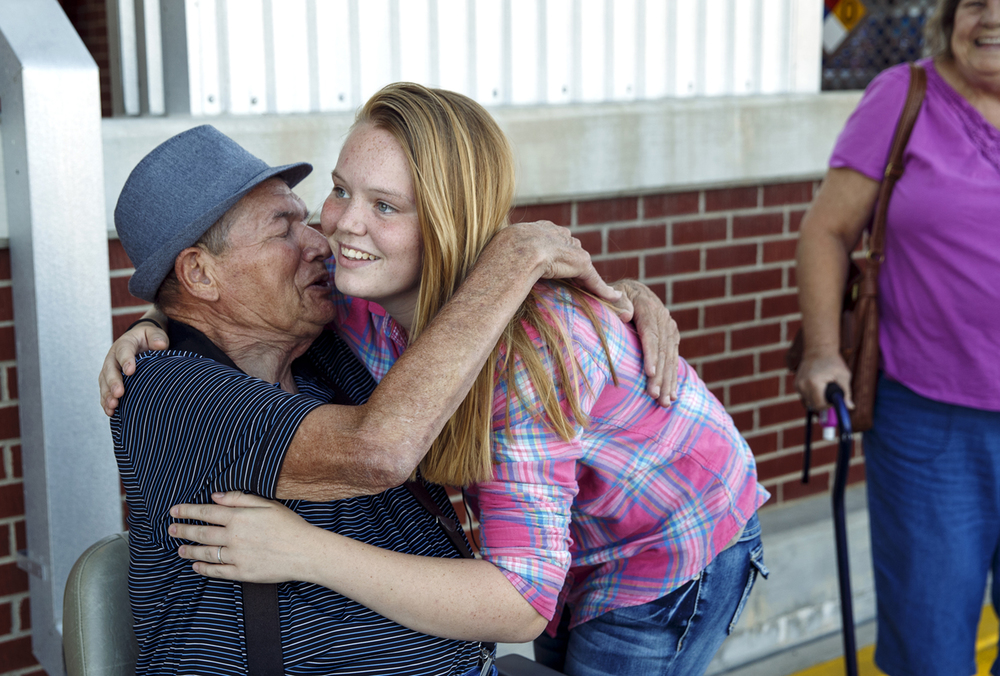 Ashley Aldridge greets Earl Moorman, 75, whom she freed from his electric wheelchair after it had gotten stuck at the railroad crossing seconds before a train crashed into it last week in Auburn, before her shopping spree at Chatham County Market Monday, Sept. 21, 2015.  Ted Schurter/The State Journal-Register