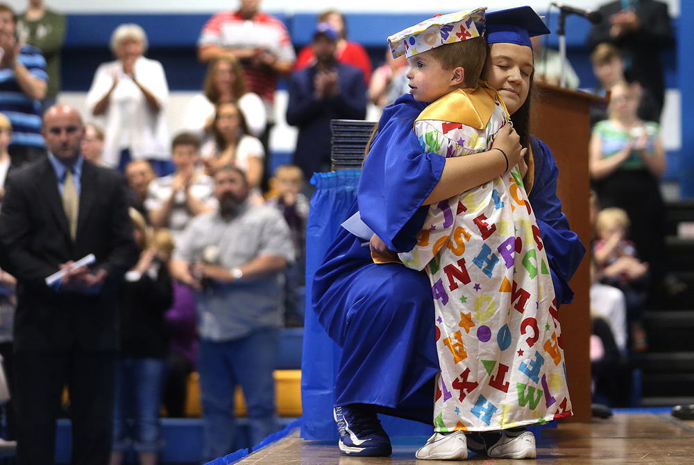 Tri-City High School Valedictorian Bethany Daniels hugs Jordan Planitz after he was presented with an honorary diploma from the school in Buffalo May 31, 2015. Planitz sufferers from a terminal brain condition and the Tri-City class of 2015 wanted the six-year-old to have a diploma of his very own. David Spencer/The State Journal-Register