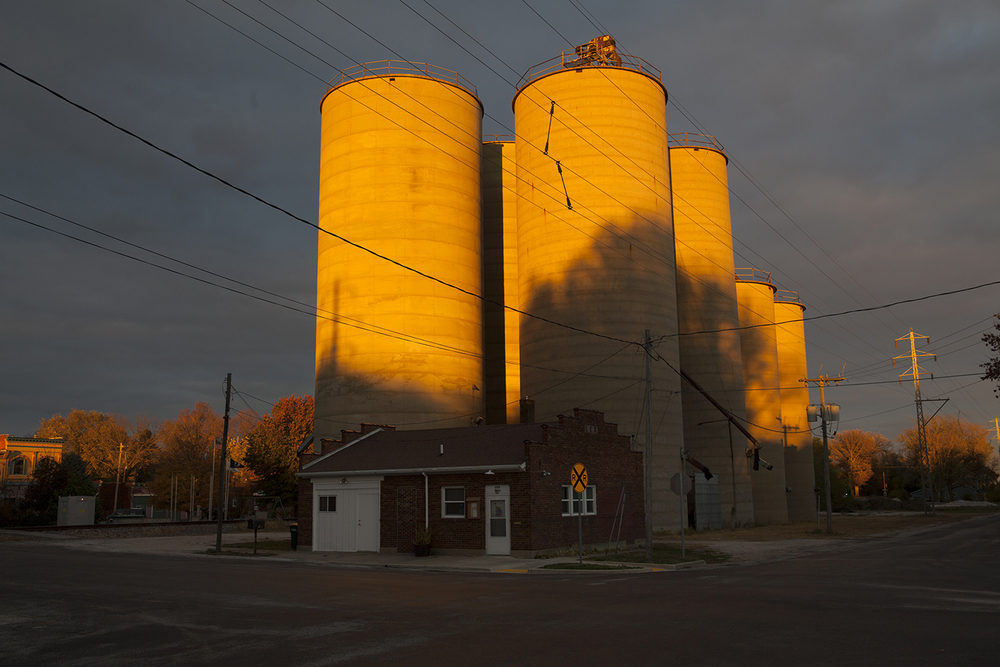The sun breaks through a layer of overcast clouds, casting a brilliant glow on grain silos in Illiopolis Thursday Oct. 29, 2015. Rich Saal/The State Journal-Register
