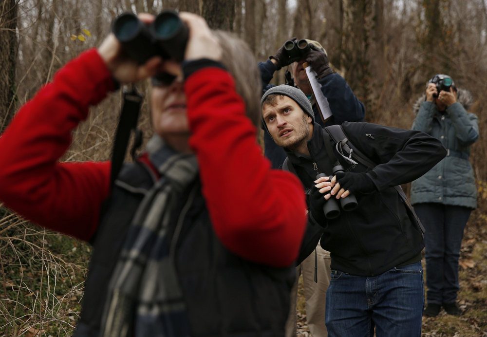 Alex Patia stoops down to get a different view during the Christmas Bird Count at Adams Wildlife Sanctuary Sunday, Dec. 20, 2015. The group spotted more than 20 different species during the event. Ted Schurter/The State Journal-Register