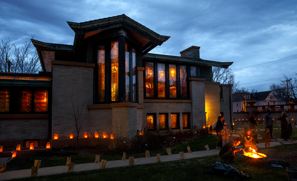 Chuck Hargan lights a fire in the courtyard at the Frank Lloyd Wright-designed Dana-Thomas House State Historic Site Sunday, Dec. 20, 2015. Gusty winds ignited some luminaria prompting site officials to stop lighting any more. Despite fewer lit luminaria, visitors still lined up to tour the site and view the holiday decorations. Ted Schurter/The State Journal-Register