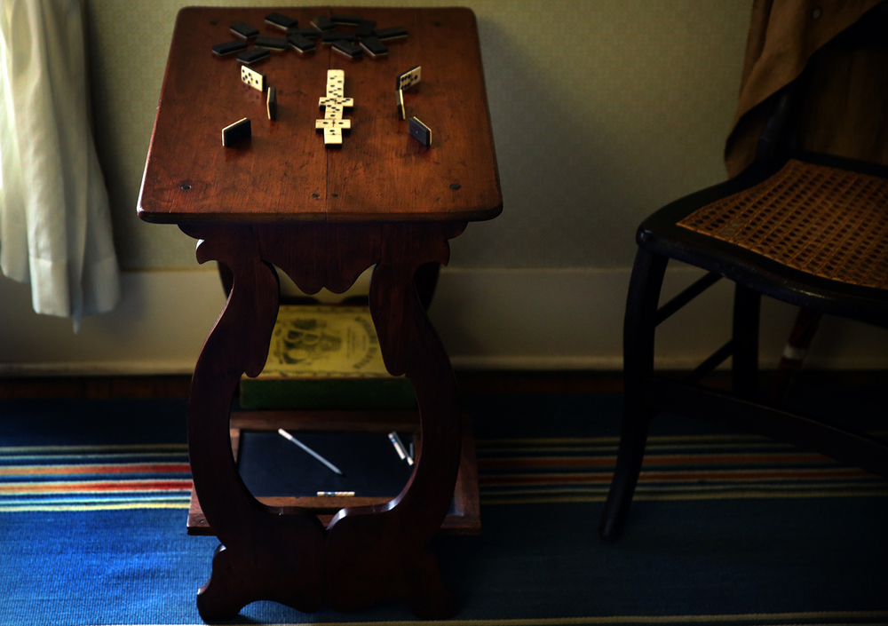 The table in the Lincoln boys bedroom is seen on Tuesday, Dec. 22, 2015 set with dominoes. The lyre-shaped uprights of the table are scarred and the uprights have been broken several times, attesting to the well-known rambunctiousness of Willie and Tad. Fees from the sale of park passes and parking at the Lincoln Home National Historic Site in Springfield funded the recent conservation of four artifacts associated with the home that were returned last week and placed back on display. A chest of drawers in Mary Lincoln's bedroom, a fancy painted Hitchcock-style dining room chair, a bedroom table belonging to Willie and Tad Lincoln and a ruffled nightcap made by Mary Lincoln for hired girl Margaret Browne were all stabilized, repaired, and cleaned by conservators working at the Park Service's conservation facility in Charles Town, West Virginia. David Spencer/The State Journal-Register