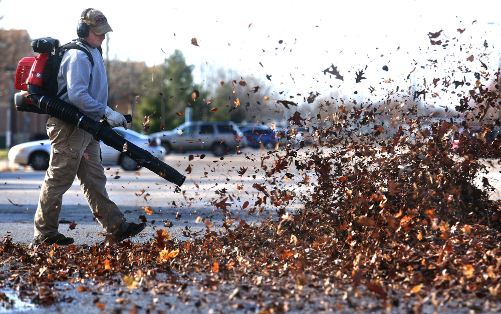 University of Illinois Springfield Grounds Maintenance department employee Dave Lock admitted to feeling a bit overdressed as temperatures inched up to 65 degrees on Monday, Dec. 21, 2015 while blowing leaves across a student housing parking lot. Lock said the job was delayed in order to accomodate students who finished up their finals and the Fall semester last week. The leaves will be used for mulch for trees across from the housing on the other side of Vachel Lindsay Drive. David Spencer/The State Journal-Register