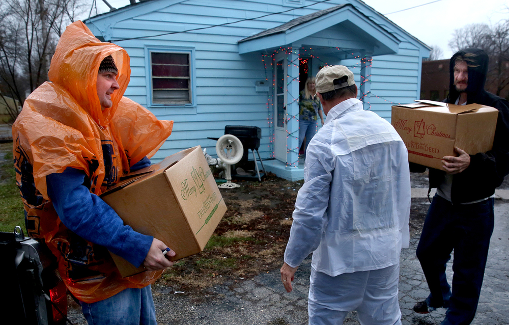 Friend-in-Deed volunteers Ira Smith of Springfield at left along with Steve Kunshek at middle delivered to a residence on North Grand Ave. West Wednesday. At right is recipient Randy Phillips. Hundreds of volunteers fanned out around Springfield on Wednesday morning, Dec. 23, 2015 to deliver food boxes as part of the 55th year of the Friend-in-Deed program helping approximately 2600 families and individuals in need this holiday season. David Spencer/The State Journal-Register