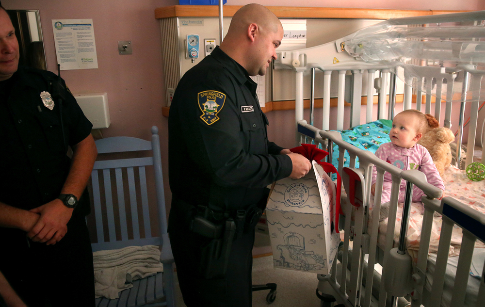 "Springfield police officer Ryan Maddox presents a teddy bear to 15-month-old patient Piper Langston of Decatur in her hospital room Wednesday afternoon. For the third year, Springfield Police officers, members of the Springfield Police Benevolent & Protective Association, sold raffle tickets and used the proceeds to purchase toys for children who are patients at HSHS St. John's Children's Hospital in Springfield. On Wednesday, Dec. 23, 2015, the officers personally delivered teddy bears- the Paw Patrol Pup ""Chase"", to 24 children at the hospital. The officers also gave six X-Boxes as well as $200.00 in gift cards to some of the older children at the hospital. David Spencer/The State Journal-Register"