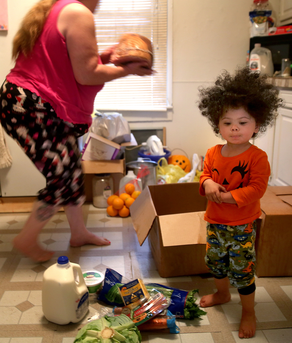 LaBella Stender, 18 months, was assisting her grandmother Barbara Stender as they placed food, including a Christmas ham, in the refrigerator of their home after receiving a FID delivery Wednesday morning. Hundreds of volunteers fanned out around Springfield on Wednesday morning, Dec. 23, 2015 to deliver food boxes as part of the 55th year of the Friend-in-Deed program helping approximately 2600 families and individuals in need this holiday season. David Spencer/The State Journal-Register